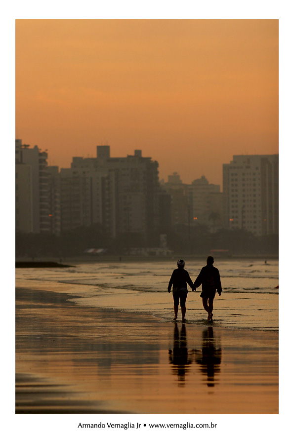 Couple walking on the beach at the city of Santos, Brazil