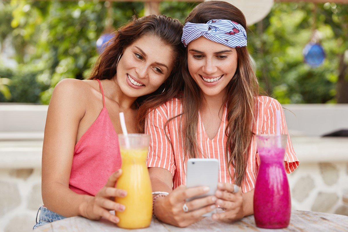 photo-of-happy-young-women-have-samesex-relations-surf-internet-on-mobile-phone-read-comments-under-post-drink-fresh-cocktails-in-cafeteria